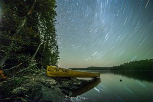 Star Trails highlight the sky as a canoe sits on the bed of Steel River near Terrace Bay