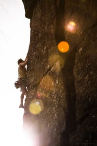 a sun flare highlights a climber on lost falls.